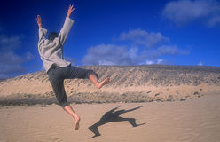 Happy Jumping girl. Happy girl jumping around the dunes in Fuerteventura Charlie Chaplin style stock photos