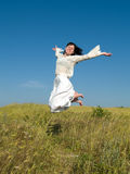 Happy Jumping Girl above Field. Happy Jumping Girl on Field looking to camera Royalty Free Stock Photography