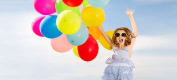 Happy jumping girl with colorful balloons. Summer holidays, celebration, children and people concept - happy jumping girl with colorful balloons outdoors Royalty Free Stock Image