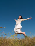 Happy Jumping Girl on Field. Happy jumping girl in green field on blue sky Royalty Free Stock Photo