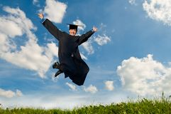 Happy jumping graduate outdoors. Young smiley graduate student in gown jumping over blue sky Stock Photography