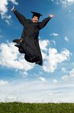Happy jumping graduate outdoors. Young smiley graduate student in gown jumping over blue sky Royalty Free Stock Photos