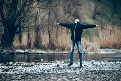 Happy jumping man in beautiful river landscape. Freedom concept Stock Photos