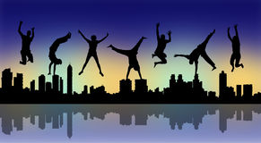 Happy jumping people with a night city silhouette. Silhouettes of young happy people jumping a big city panoramic silhouette by night Royalty Free Stock Photo