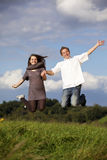 Happy jumping teenage couple Royalty Free Stock Photos