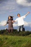 Happy jumping teenage couple royalty free stock photos