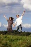 Happy jumping teenage couple royalty free stock image