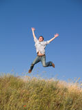 Happy Jumping Teenager Above Hill. Happy jumping male teenager above green grass hill Royalty Free Stock Photo