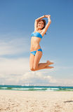 Happy jumping woman on the beach. Bright picture of happy jumping woman on the beach Stock Photography