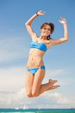 Happy jumping woman on the beach. Bright picture of happy jumping woman on the beach Royalty Free Stock Images