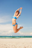 Happy jumping woman on the beach Stock Photo