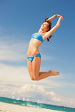 Happy jumping woman on the beach. Bright picture of happy jumping woman on the beach Stock Image