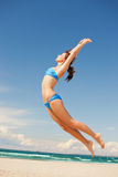 Happy jumping woman on the beach. Bright picture of happy jumping woman on the beach Royalty Free Stock Image