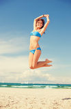 Happy jumping woman on the beach. Bright picture of happy jumping woman on the beach Royalty Free Stock Photography
