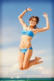 Happy jumping woman on the beach. Bright picture of happy jumping woman on the beach Royalty Free Stock Photos