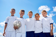 Happy Junior Football Team Posing. Portrait of junior football team posing smiling at camera with ball against clear blue sky in sunlight Stock Images