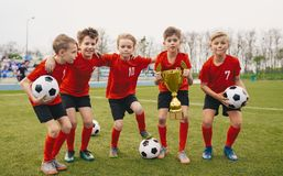 Free Happy Junior Sports Team. Young Boys In Soccer Team Holding Golden Cup And Soccer Balls Royalty Free Stock Image - 159118446