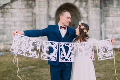 Happy just married bride and groom holding artistic papercut love letters Royalty Free Stock Photography