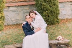Happy just married couple in autumn park. Elegant bride sitting on knees of her handsome new husband Stock Photos