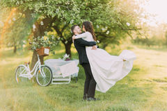 Happy just married couple dancing on lawn in green sunny park. Bicycle near decorated tree at background.  Stock Image