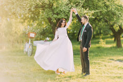 Happy just married couple dancing on lawn in green sunny park. Bride's dress flatter while she moves Royalty Free Stock Images