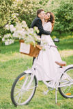 Happy just married couple holding each other in park. Bicycle with wedding decoration on foreground Royalty Free Stock Photo
