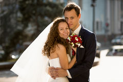 Happy just married couple hugging on street Stock Photos
