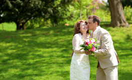 Happy just married couple kissing. In park at sunny day Royalty Free Stock Photos
