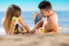 Happy just married couple lay on the beach eating apple, playing with little dog Royalty Free Stock Photography