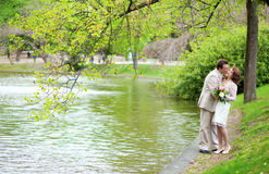 Happy just married couple in park near the water Stock Photography