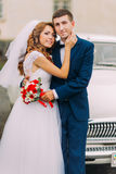 Happy just married couple posing in the background of vintage car.  Stock Images
