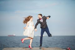 Happy just married young wedding couple celebrating and have fun at beautiful beach sunset. Happy just married young couple celebrating and have fun at beautiful Stock Photography