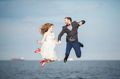 Happy just married young wedding couple celebrating and have fun at beautiful beach sunset. Happy just married young couple celebrating and have fun at beautiful Stock Photo