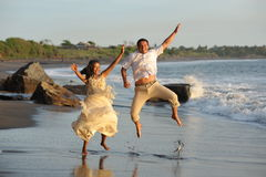 Happy just married young couple jumping Royalty Free Stock Images