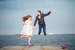 Happy just married young wedding couple celebrating and have fun at beautiful beach sunset. Happy just married young couple celebrating and have fun at beautiful Stock Images