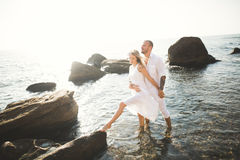 Happy just married young wedding couple celebrating and have fun at beautiful beach sunset Stock Image