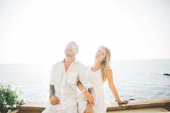Happy just married young wedding couple celebrating and have fun at beautiful beach sunset Stock Photos