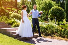 Happy just married young wedding couple having fun in the park. Bride and groom together, love and marriage theme. Happy just married young wedding couple Stock Photos