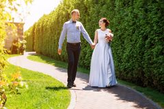 Happy just married young wedding couple having fun in the park. Bride and groom together, love and marriage theme. Royalty Free Stock Images