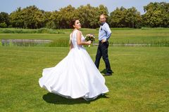 Happy just married young wedding couple having fun in the park. Bride and groom together, love and marriage theme. Stock Photography