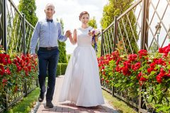 Happy just married young wedding couple having fun in the park. Bride and groom together, love and marriage theme. Royalty Free Stock Photo