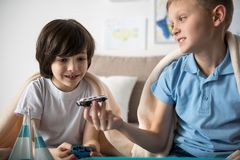 Glad schoolboys having fun time. Happy juvenile boy showing toy car to his friend, boy is looking at it with admiration Stock Photography
