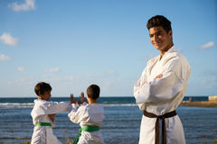 Happy Karate Sport Instructor Watching Young Boys Fighting. Teacher training children in karate and traditional martial arts. Simulation of fight near the sea Royalty Free Stock Photography