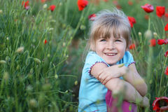 Happy kid. Blond girl on the field of red poppies Stock Photography