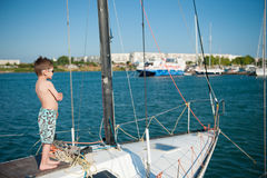 Happy kid aboard luxury yacht in sea port in summer day Stock Photos