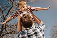 Happy kid being in hands of his father. Like a plane. Delighted child keeping smile on his face and looking downwards while holding hands in the air Royalty Free Stock Photos