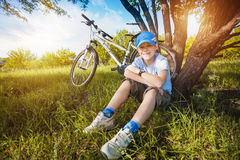 Happy kid with a bicycle resting under a tree Stock Photo