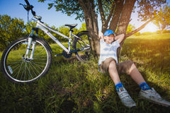 Happy kid with a bicycle resting under a tree Stock Photos