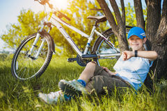 Happy kid with a bicycle resting under a tree Royalty Free Stock Image