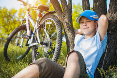 Happy kid with a bicycle resting under a tree Stock Image